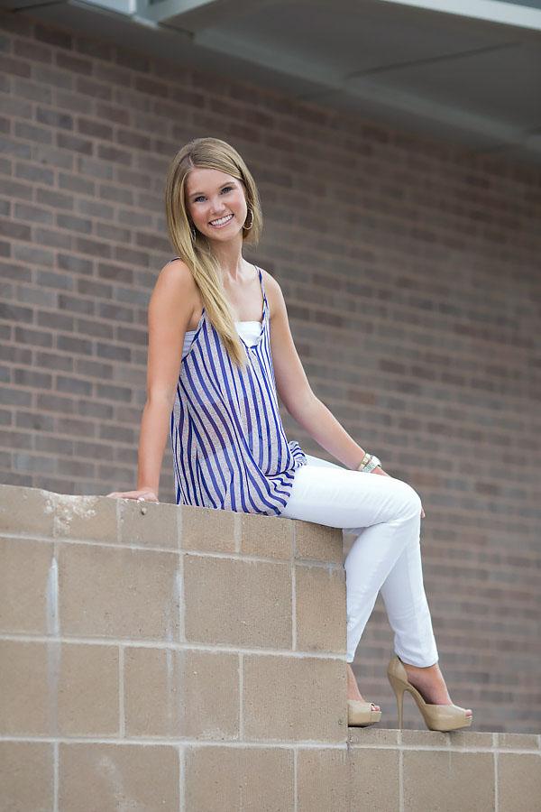 blonde female senior portraits blue striped blouse white jeans brick wall