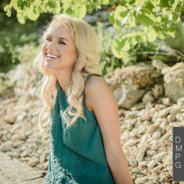 senior photos austin blonde wearing green shirt and black pants for her ut graduation photos