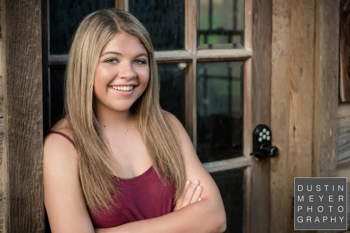 blonde girl senior portraits backlit sun flare flair maroon shirt smile
